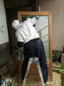 まずは、玄関ドアから。ガラスに自然塗料が付かないよう、マスキングテープを貼り、施工します